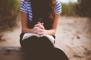 Bild på kvinna som ber med Bibel i knät